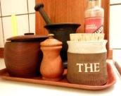 Teburk (5 kr), smörbytta i teak (15 kr), mortel i gjutjärn (140 kr) på teakbricka.